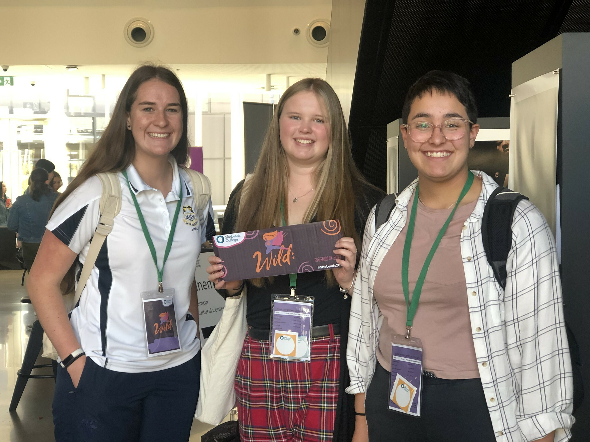 photos of three girls holding a she leads conference sign that says wild