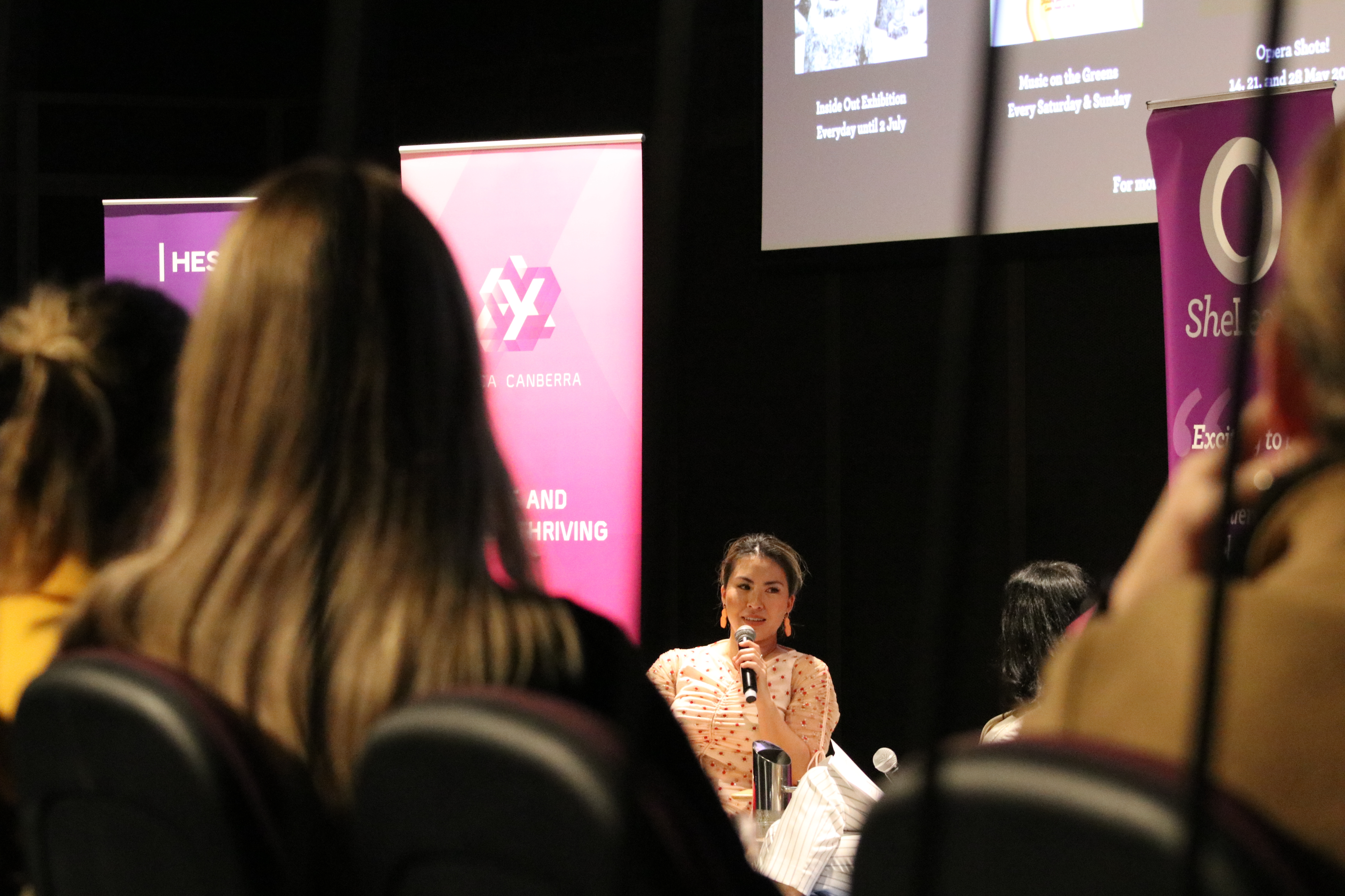 Photo shows an audience (from behind) listening to Yumiko Kadota speak at the She Leads In Conversation